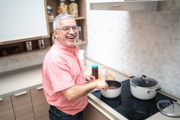 Portrait of a senior man cooking brigadeiro at home Portrait of a senior man cooking brigadeiro at home stay at home father stock pictures, royalty-free photos & images