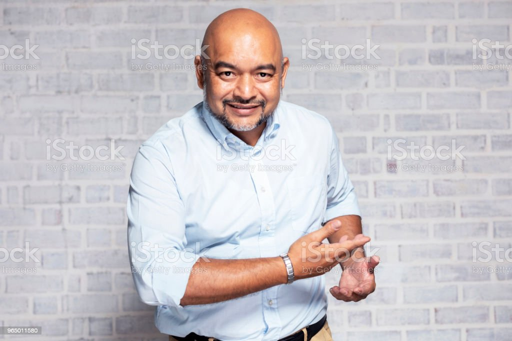 Portrait of a senior man gesturing welcome stock photo