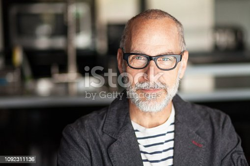 Portrait Of A Senior Man Looking At The Camera. He's confident. He's working at home. Kitchen background. He's wearing eyeglasses