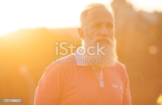 Portrait of a bearded senior man outdoors