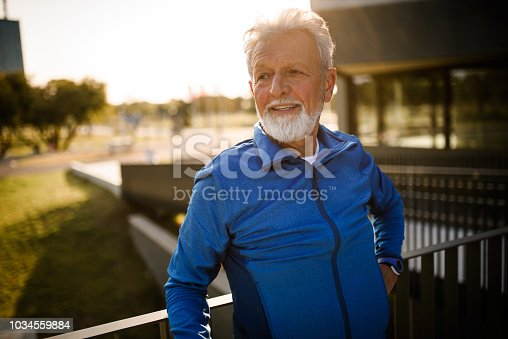 Portrait of a senior man looking away. He is relaxing after work out.