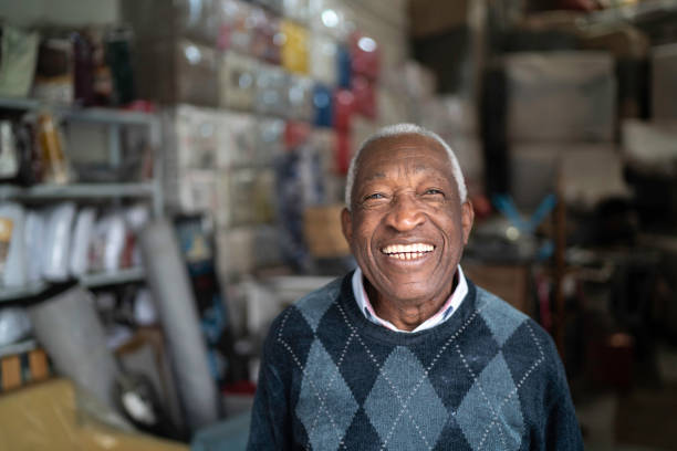 Portrait of a senior man standing in an upholstery workshop stock photo