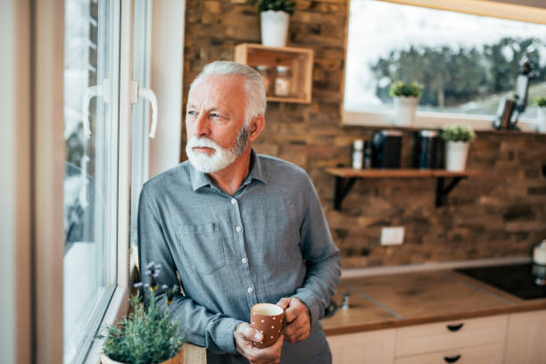 portrait of a senior man standing in the kitchen and looking through window, holding a cup of coffee or tea on winter day. - old men window imagens e fotografias de stock
