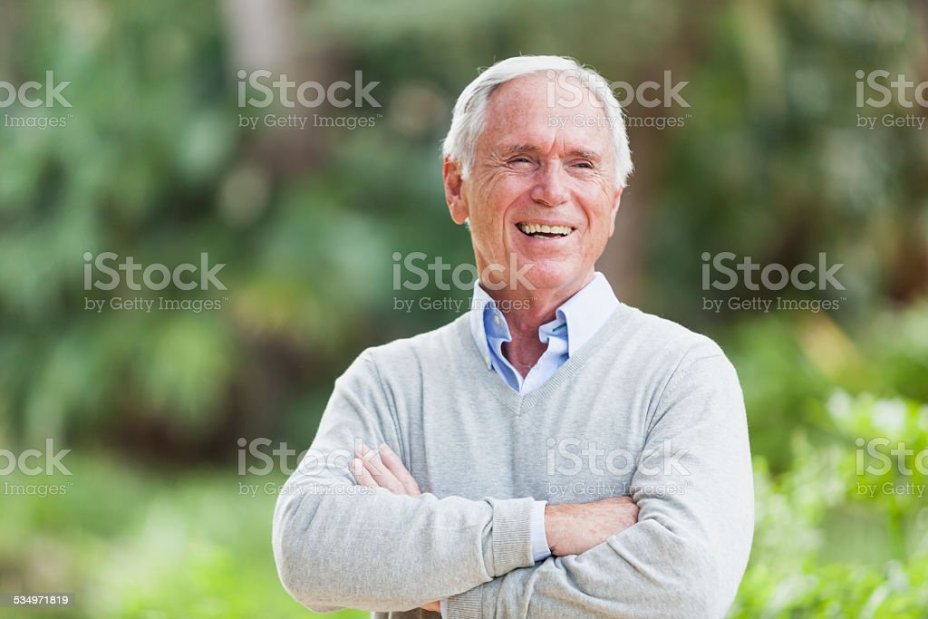 Portrait of a senior man standing with arms crossed stock photo