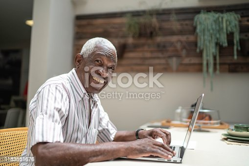 1127582480istockphoto Portrait of a senior man using laptop at home 1183551676