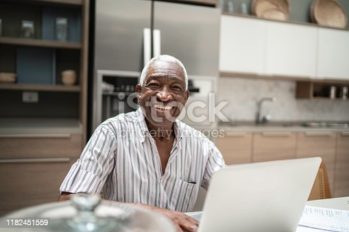 1127582480istockphoto Portrait of a senior man using laptop in the kitchen table 1182451559