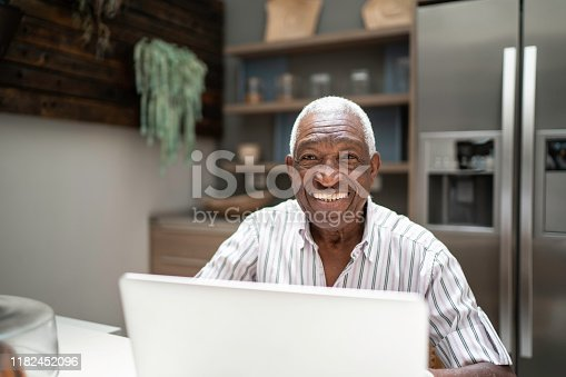1127582480istockphoto Portrait of a senior man using laptop in the kitchen table 1182452096