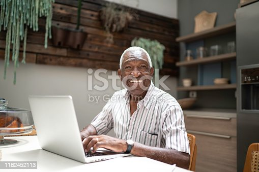 1127582480istockphoto Portrait of a senior man using laptop in the kitchen table 1182452113