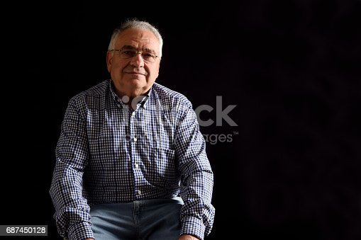 istock Portrait of a senior man with black background 687450128