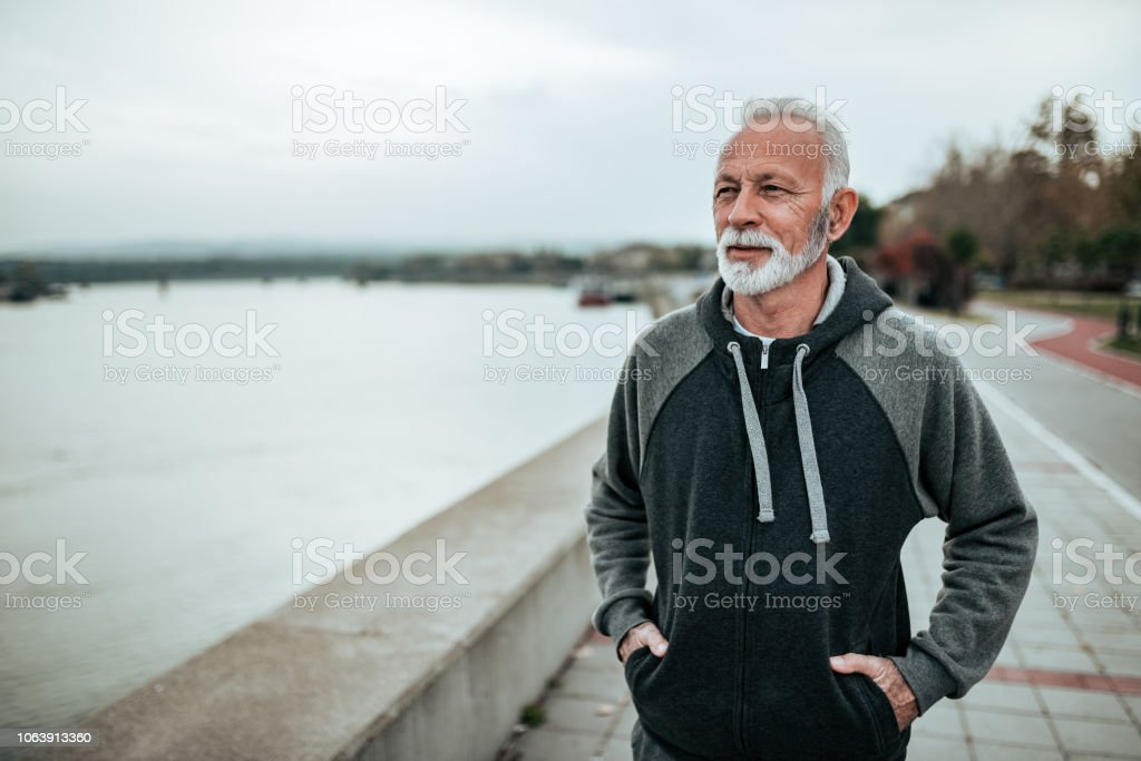 Portrait of a senior sportsman walking near the river in the city. Portrait of a senior sportsman walking near the river in the city. Active Lifestyle Stock Photo