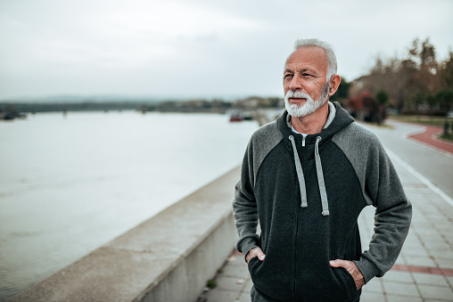 Portrait Of A Senior Sportsman Walking Near The River In The City Stock Photo - Download Image Now