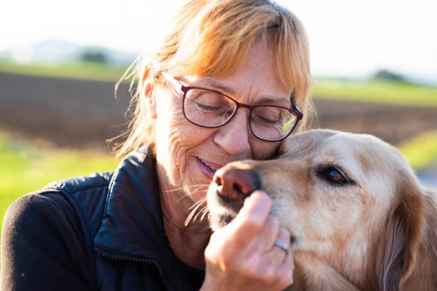 Portrait einer älteren Frau in der Natur, genießen Sie ihre Zeit mit ihrem Hund – Foto