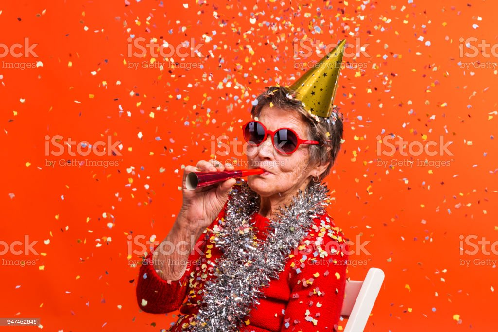 Portrait of a senior woman in studio on a red background. Party concept. stock photo