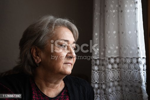 istock Portrait of a senior woman on front of the window 1126667392
