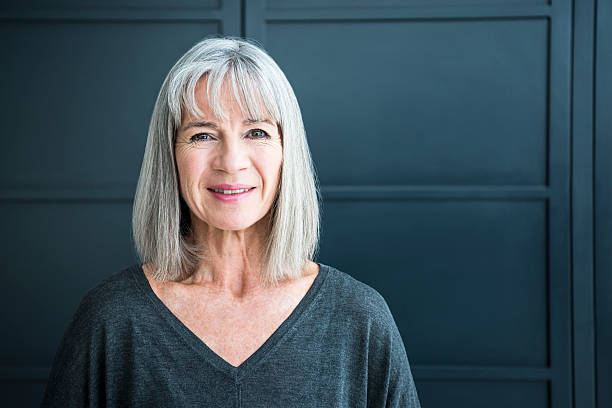 Portrait of a senior woman smiling towards camera Senior woman in her 60s with grey bobbed hair, smiling at the camera. She looks content and relaxed, in front of a grey background. 60 64 years stock pictures, royalty-free photos & images