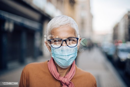 Portrait of an elderly woman in the city, wearing a protective face mask and the eyeglasses