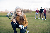Senior woman playing golf with her friends.