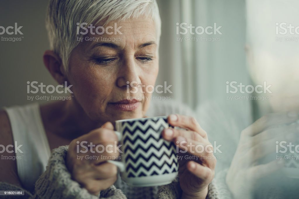 Portrait of a senior woman with coffee cup by the window. stock photo