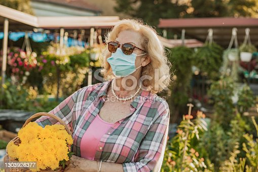 istock Portrait of a senior woman with protective face mask buying flowers at the market 1303926377