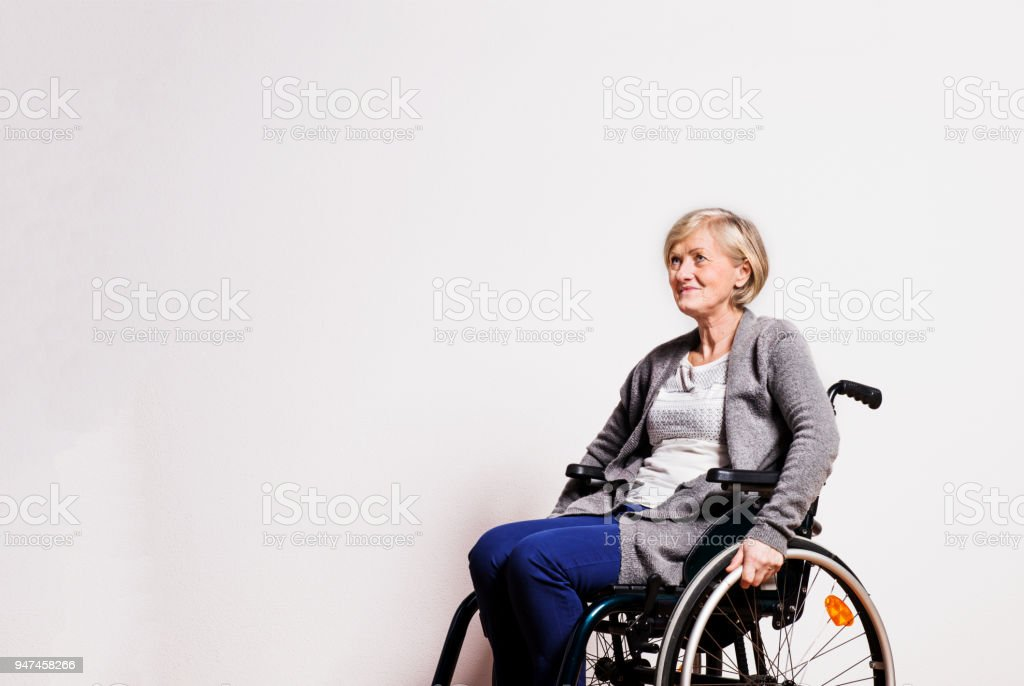 Portrait of a senior woman with wheelchair in studio. stock photo