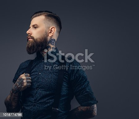 istock Portrait of a serious handsome old-fashioned hipster in shirt and suspenders. 1018774786