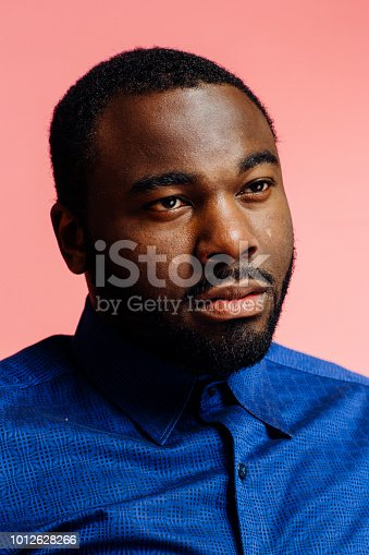 Portrait of a serious, handsome man in blue shirt looking off camera, isolated on pink background