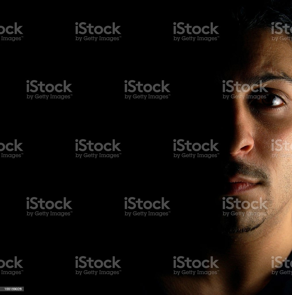 Portrait of a serious man with half his face in the shadows stock photo