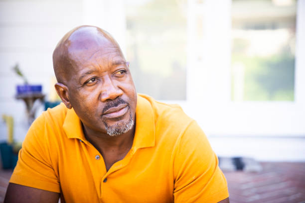 Portrait of a Serious Mature Black Man A mature black man looks out while standing on his porch serious stock pictures, royalty-free photos & images