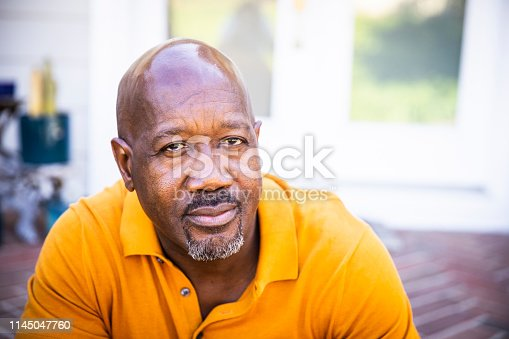 A mature black man looks out while standing on his porch