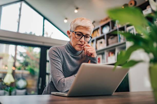 Retrato de una mujer seria de la tercera edad mirando a la computadora portátil. - foto de stock
