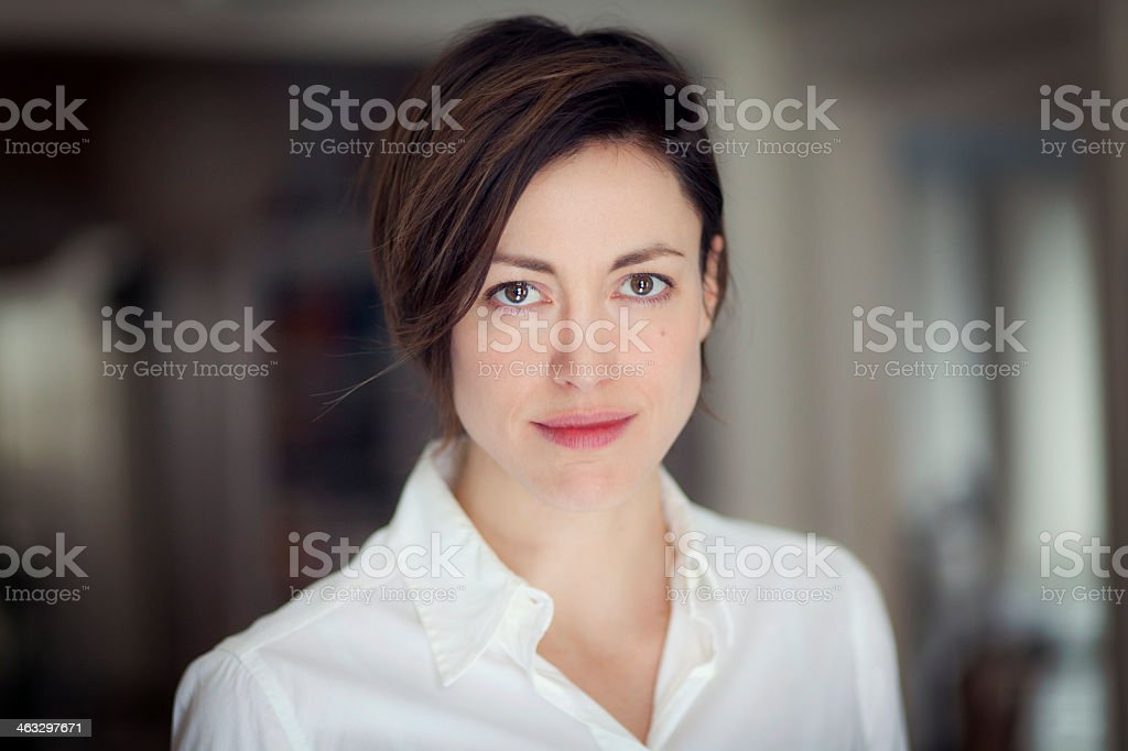 A portrait of a serious woman wearing a white collared shirt stock photo