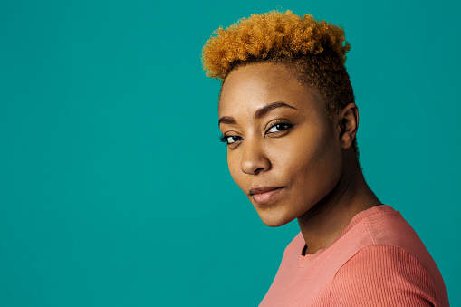 Portrait of a serious young african female with cool short hair looking at camera, against studio background