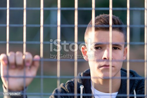 Portrait of a serious young male leaning behind a chain link fence while looking camera