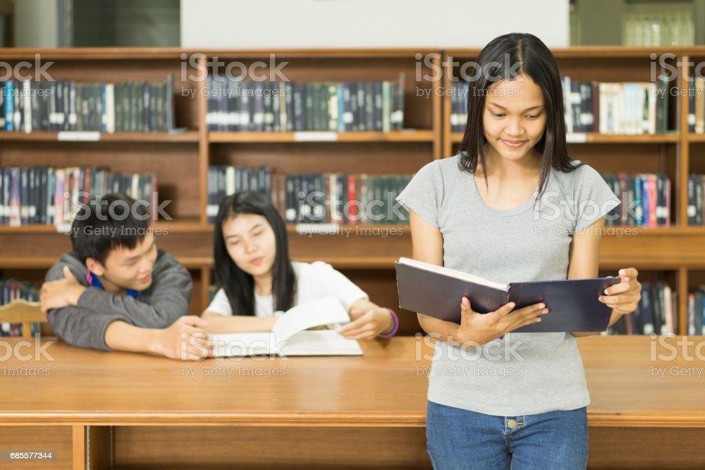 도서관에서 책을 읽고 심각한 젊은 학생의 초상화 royalty-free 스톡 사진