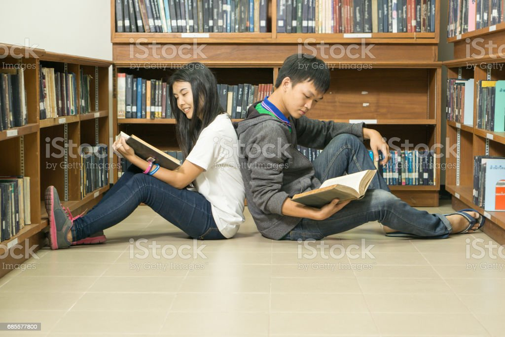Portrait of a serious young student reading a book in a library royalty-free stock photo