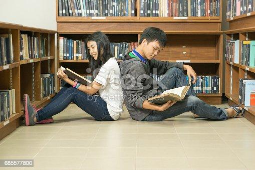 Portrait Of A Serious Young Student Reading A Book In A Library - Fotografias de stock e mais imagens de 20-24 Anos
