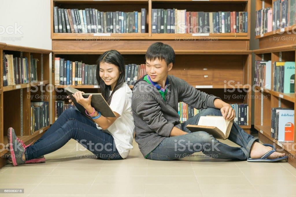 一個認真的年輕學生在圖書館看書的肖像 免版稅 stock photo