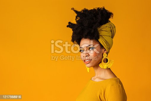 Portrait of a serious young woman with big yellow tassel beaded earrings and afro hair wrapped with head wrap scarf, isolated on yellow background