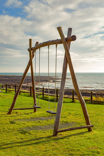 An empty set of swings in a coastal park in Fife, which we encountered while on a staycation. The swings here are empty.