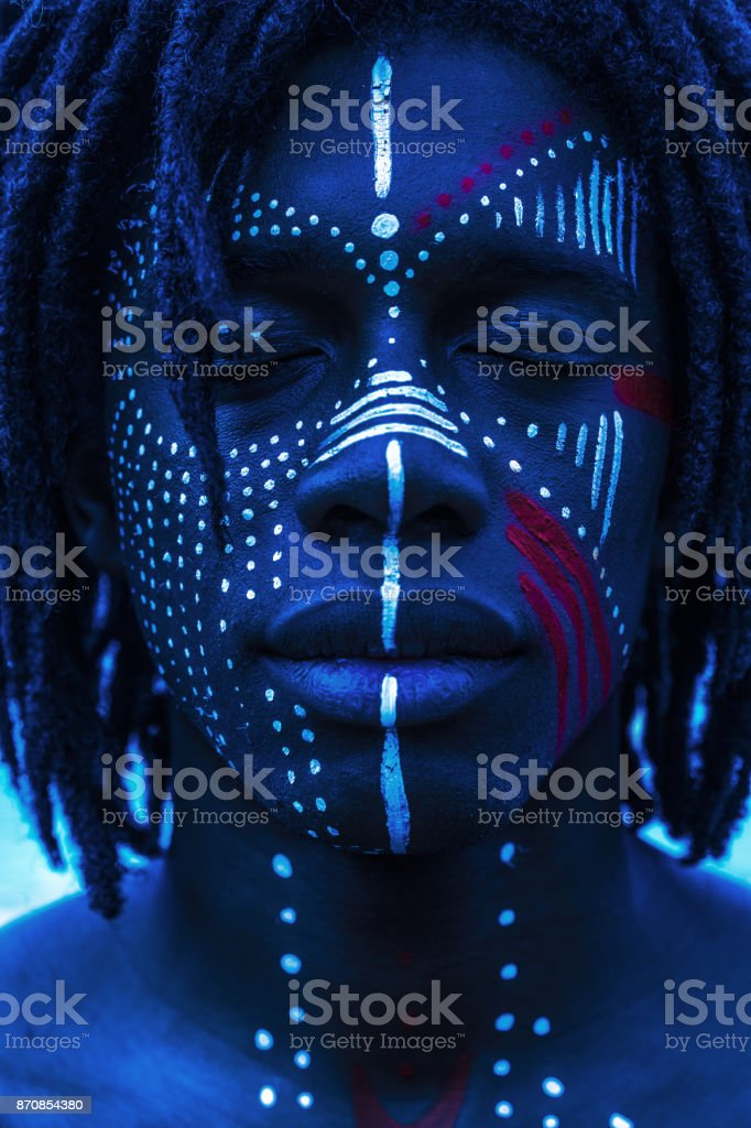 Portrait of a Sexy African man with traditional face paint and neon lighting stock photo