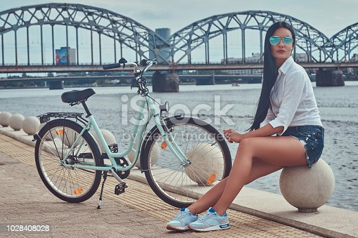 istock Portrait of a sexy brunette girl dressed blouse and shorts in sunglasses, sitting on a quay against the bridge. 1028408028