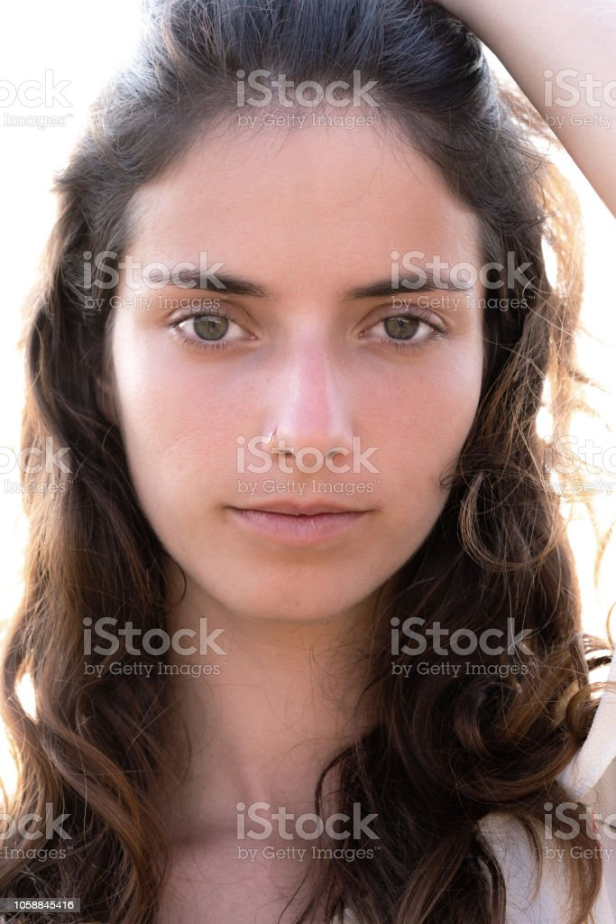 Portrait of a sexy girl sliding her hands through her hair with a fixed gaze into the camera stock photo