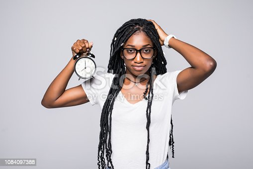 istock Portrait of a shocked young afro american woman holding alarm clock isolated over gray background 1084097388