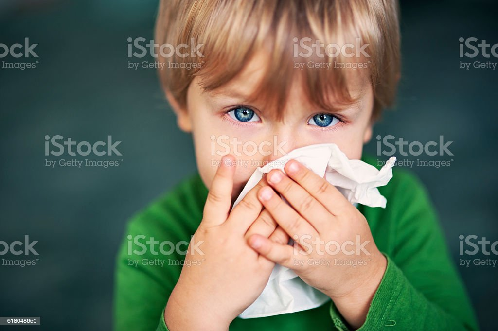 Portrait of a sick boy cleaning his nose stock photo