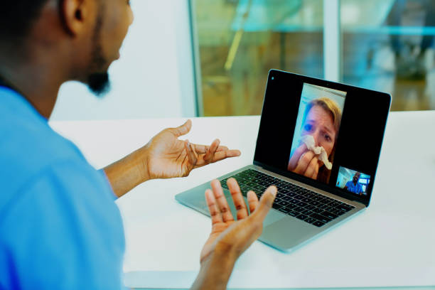 Portrait of a sick patient coughing into tissue being helped via tele medicine by a male doctor wearing blue scrubs uniform using laptop Portrait of a sick patient coughing into tissue being helped via tele medicine by a male doctor wearing blue scrubs uniform using laptop visit stock pictures, royalty-free photos & images