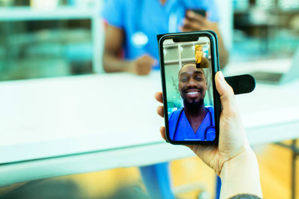 portrait of a sick patient coughing into tissue being helped via tele medicine by a male doctor wearing blue scrubs uniform using smartphone mobile phone - carlos david stock pictures, royalty-free photos & images