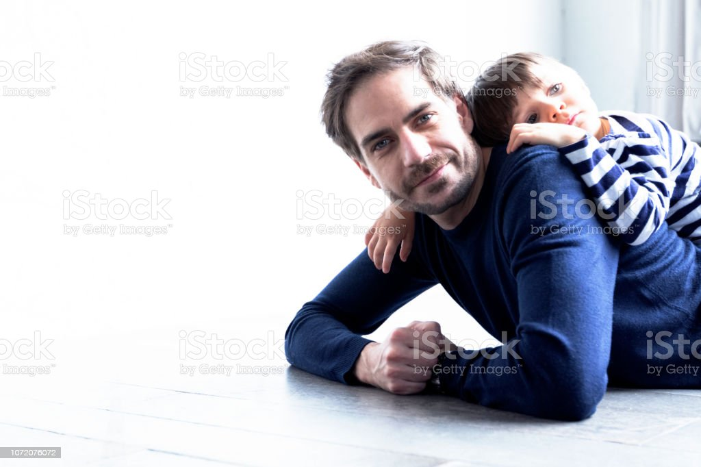 Relationship, Childhood, Portrait - Cute kid lying on his father's...