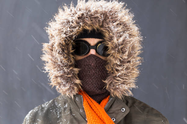 Portrait of a single male winter adventurer with vintage style goggles Portrait of a single male winter adventurer wearing a warm green coat with fur hood, a blue ski cap, an orange scarf and black retro style goggles hood clothing stock pictures, royalty-free photos & images