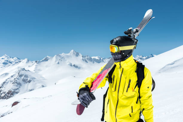 A portrait of a skier in a protective helmet and glasses is a mask and scarf with skis on his shoulder in the snow-capped mountains of the Caucasus. Skiing stock photo