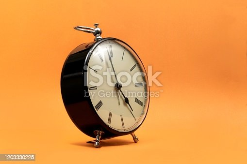 816405814 istock photo A portrait of a small old fashioned antique alarm clock with roman numbers on the dial on an orange background. The hands of the clock are almost pointing to 5 o'clock. 1203330225